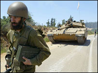 An Israeli soldier walks along a road followed by a tank near the northern Israeli town of Zarit close to the Israeli-Lebanese border