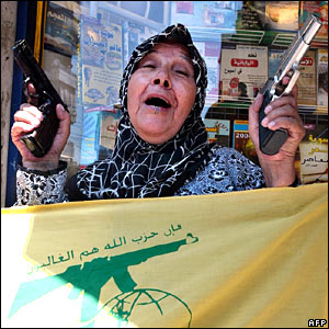 Beirut woman with Hezbollah flag waves guns