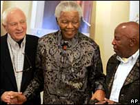 Former South African President Nelson Mandela, centre, stands with photographers Jurgen Schadeberg, left, and Alf Kumalo right