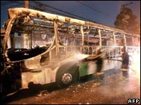Firefighters spray a burned out bus in Sao Paulo