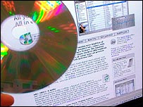 A recordable CD held in front of a computer
