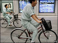 Japanese men cycle past an electronic board showing share prices