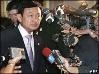 Prime Minister Thaksin Shinawatra talks to reporters