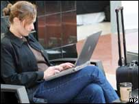 Woman using laptop in airport, AP