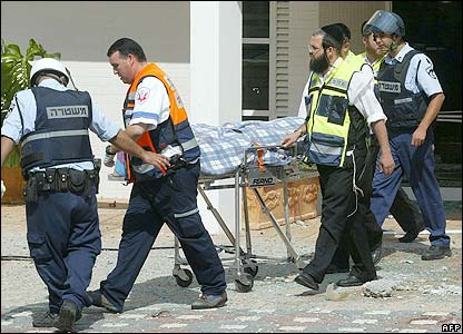 The body of a woman is removed from an apartment block in Nahariya, Israel