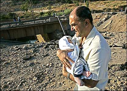 A Lebanese man carries a baby over a damaged bridge