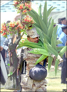 An Iraqi soldier holding a decorative flowers