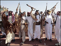 Armed Iraqi tribesmen celebrating during a handover ceremony