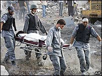 Lebanese medics carry away a victim of an Israeli air strike