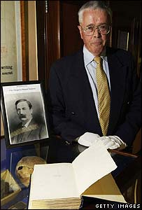 Nevill Swanson next to a portrait of his great-grandfather