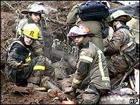 Rescue workers try to recover the body of one of 10 deaths in a landslide