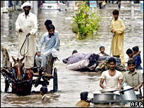 People wade through a flooded street in Lahore