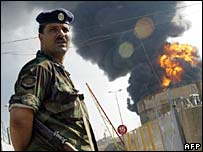 Lebanese soldier in front of burning fuel tanks at Beirut airport