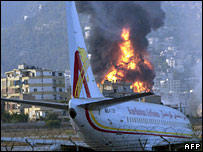 Plane at Beirut airport and burning fuel tank in background