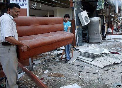 Lebanese citizens clean their shops in the Beirut suburbs of Dahyieh Al-Junubiya