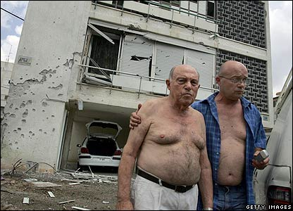 Israeli Adam Shuster (left) is helped by a neighbour after their apartment building in Nahariyya is hit by a rocket