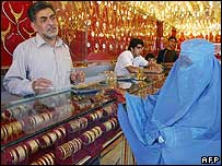 An Afghan woman buys gold jewellery at a Kabul gold market
