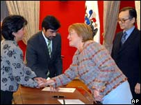 Michelle Bachelet (r) swears in Yasna Provoste, as Belisario Velasco looks on