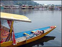 Boy sleeps in his boat in Srinagar's Dal Lake