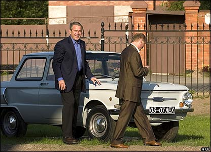George W Bush (left) with Vladimir Putin pass a Zaporozhets