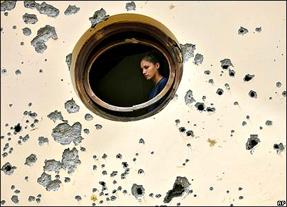 Woman looking out of rocket damaged window in Israel