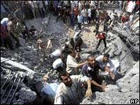 People climb in rubble of destroyed building