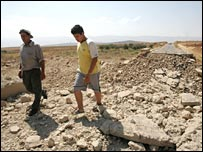 Lebanese men walk next to the wrecked bridge struck by Israeli planes in the town of Hermel in the Bekaa valley, north-east of Beirut