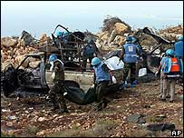 UN peacekeepers inspect the vehicles hit in an Israeli air raid near Tyre, Lebanon