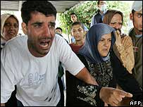 Lebanese civilians react as they look at the bodies of those killed