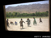 Afghan children pick up sweets thrown from a US vehicle