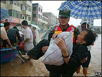 A soldier evacuates a woman from floods in China's Hunan province