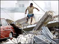 A Lebanese youth inspects the rubble of a destroyed residential building following Israeli air strikes early on 16 July 2006 in the southern Lebanese city of Tyre