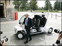 US President Bush steps out of a golf cart he drove to a meeting
