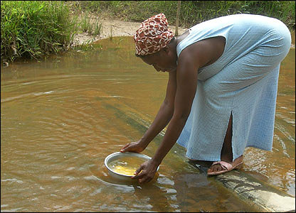 A woman collects water in a contaminated river