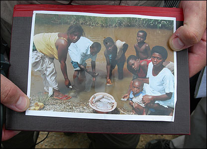 A photograph showing people picking up fish that have died from polluted river water