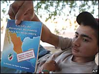 Un migrante del estado mexicano de Sinaloa, sostiene un folleto que detalla los derechos de los migrantes