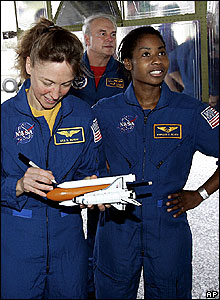 Astronaut Lisa Nowak signs a model of a shuttle, with colleague Stephanie Wilson