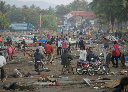 Residents walk through a street littered with debris in Pangandaran