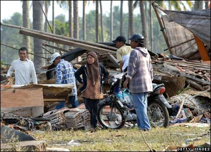 Local residents look for their belongings n the wreckage of a collapsed house