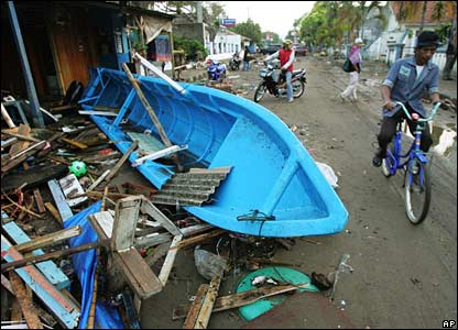 A cyclist rides past by a boat swept ashore by the tsunami