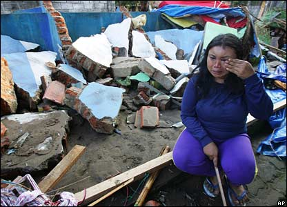 A woman cries as she sits in the rubble of her house