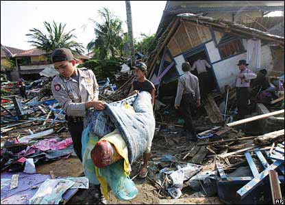 Indonesian police help residents sort through the debris