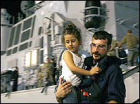 An Italian Navy man carries a girl from the Italian warship Durante de la Penne after it arrived at port in Cyprus.