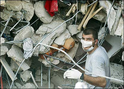 A worker looks for bodies in the wreckage of building in Tyre, Lebanon