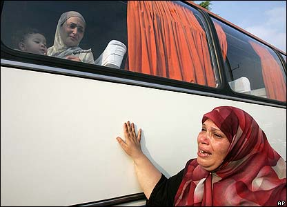 A Lebanese woman cries as her daughter and grandchild are evacuated