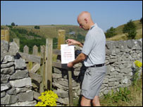 A ranger puts up a sign prohibiting moorland access