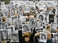 People hold photographs of the victims aloft at the ceremony in Buenos Aires