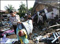 Indonesian police help villagers clear debris in Pangandaran, Java