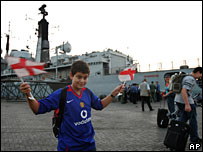 British boy waves flags next to HMS Gloucester