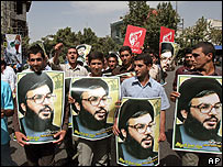 Iranian men hold posters of Hezbollah leader Sheik Hassan Nasrallah at an anti-Israeli protest in Tehran